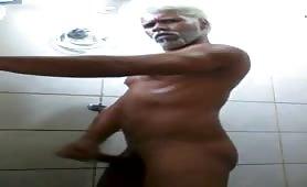 Mature man masturbates in a public restroom