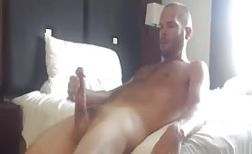 Hot stud stroking his cock on the bed