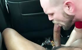 Bearded white dude blowing a tasty black cock in his car